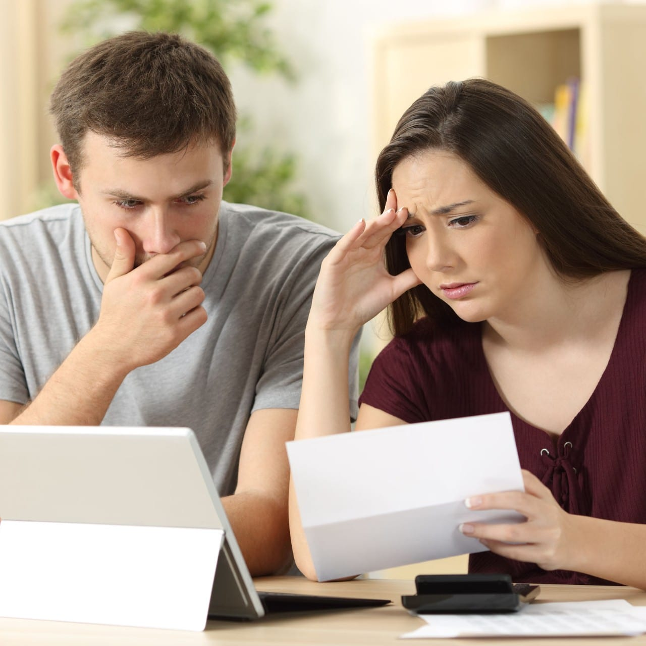 couple panicking over filing a home insurance claim as they file it