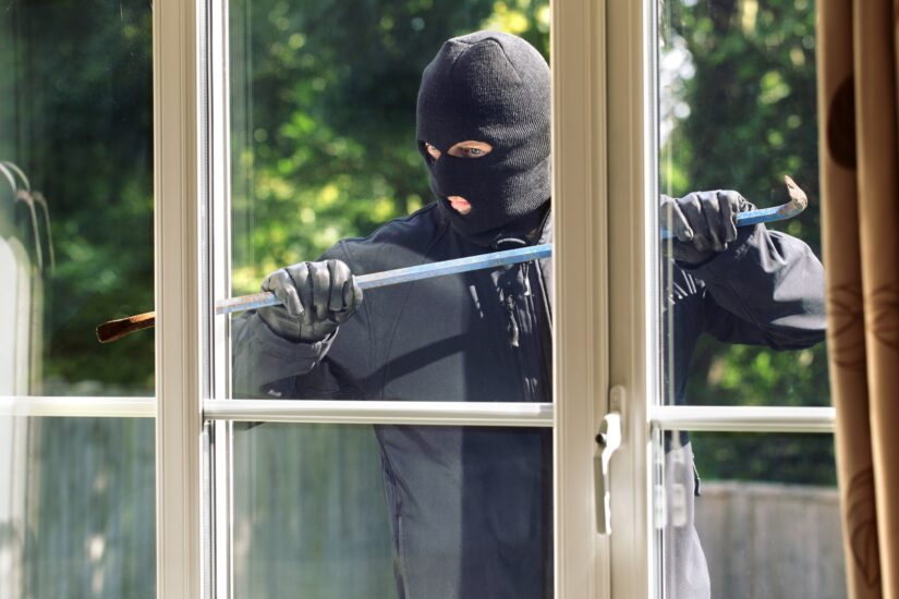 a thief in the mask trying to break in the house